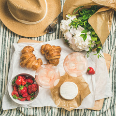 French style summer picnic setting. Flat-lay of glasses of rose wine, strawberries, croissants, brie cheese on board, hat, sunglasses, peony flowers, top view, square crop. Outdoor gathering concept