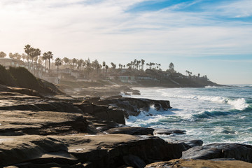 Windansea Beach eroded cliffs and rock formations on a hazy morning in La Jolla, California.