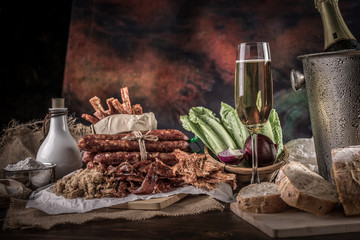 Champagne with delicious pieces of sliced ham, sausage, tomatoes, salad and vegetable - Meat platter with selection - Cutting sausage and cured meat