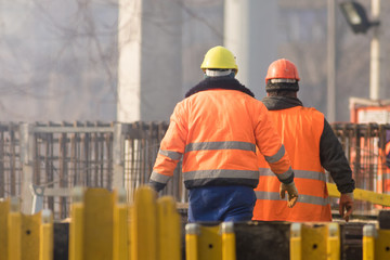 Two workers in orange at the reconstruction area