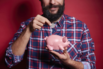 Unrecognizable man inserting coin into piggy bank