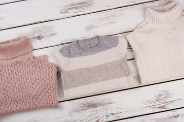 Woolen sweaters on wooden shelf