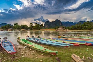 long tail boats on sunset at Song river, Vang Vieng, Laos.