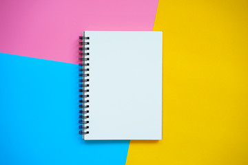 Top view of Blank notebook on colorful background pink blue yellow with copy space. Wall mural