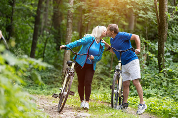 Senior marriage with bicycles kissing fondly