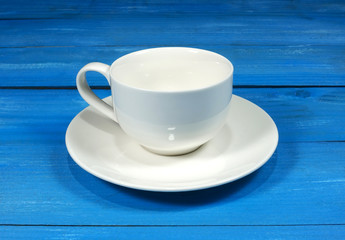 Empty white cup and saucer on blue wooden background.