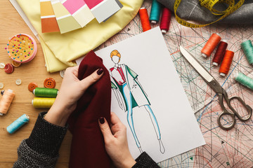 Female fashion designer working with fabric sample and drawn illustration Wall mural