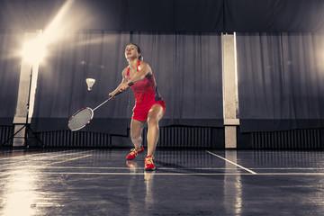 Young woman playing badminton at gym