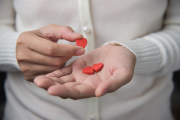 Female hands is holding pills.