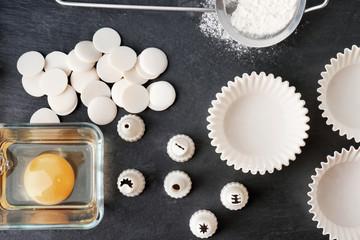Kitchen utensils and ingredients for pastries on dark background