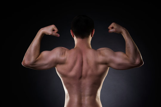 Handsome bodybuilder posing on black background, perfect muscular male back
