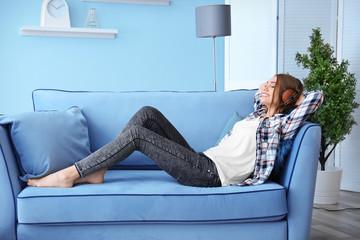 Young woman listening to music while relaxing on sofa at home