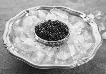 Black caviar served with ice on metal tray