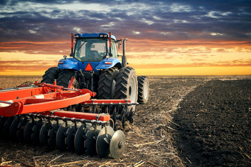 Tractor plowing field on sunset background