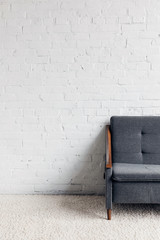 cropped shot of couch in living room with white brick wall, mockup concept