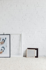 pictures in frames leaning on white brick wall, mockup concept