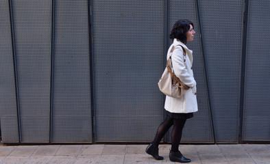 woman walking next to an iron texture wall