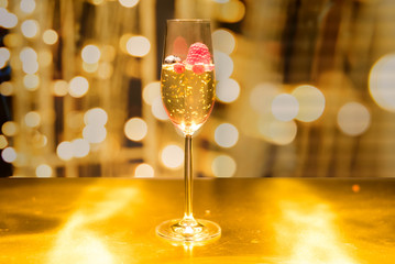 Champagne with Crystal Sparkle Gold floating and raspberry berry Cherry Blossom See the golden concept of gold color.