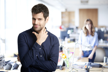 Young professional man. Confident young financial assistant businessman wearing shirt and looking at camera while standing at the office. Unrecognizable businesswoman standing at the background.