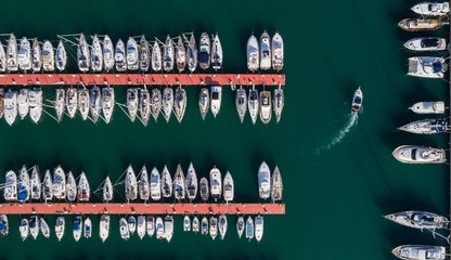 Boats moored along the jetty at harbor