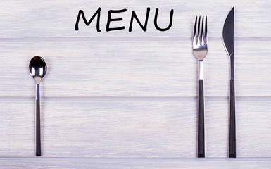 The word Menu written on wooden table, between covered kitchen on white wooden table. Menu. Food