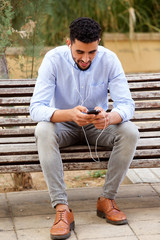 cool young North African man sitting on bench listening to music with headphones and mobile phone