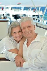 Smiling elderly couple resting on yacht