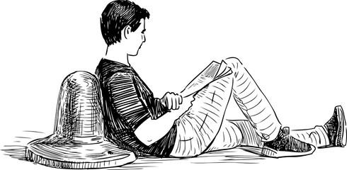 A young man reads a newspaper on an embankment