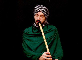 Muslim man with turban playing ney - Traditional sufi music