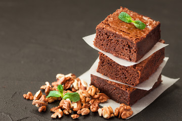 Chocolate brownie square pieces in stack on white plate with walnuts, decorated with mint leaves and cocoa on black background. Delicious dessert. Dark mood. Close up photography. Selective focus