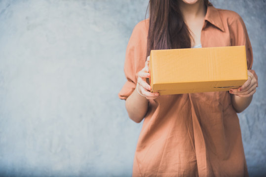 Woman holding parcel box for delivery to customer by logistic service. small business entrepreneur SME distribution warehouse concept. small  owner home office and Online marketing product theme