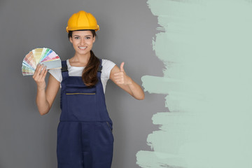 Female decorator holding color palette samples against grey background