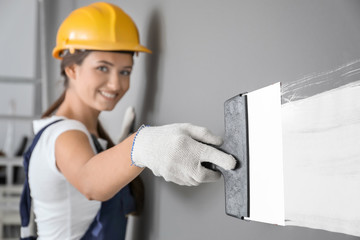 Young female decorator working with spatula indoors