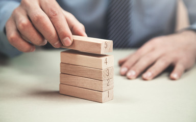 Man stacking wooden blocks. Development concept.