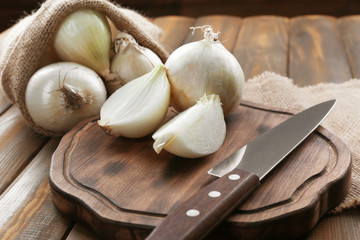 Composition with fresh onion on wooden board