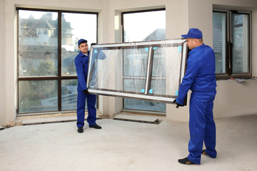 Construction workers carrying window glass indoors