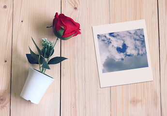 Rose in white pot and cloud shape heart picture on wood background.
