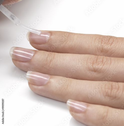 applying transparent nail polish on nails