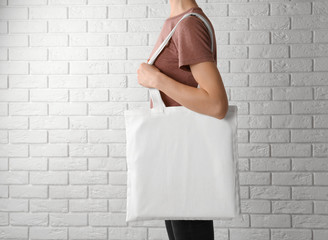 Woman with cotton bag near white brick wall. Mockup for design
