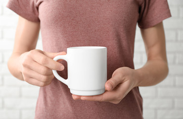 Woman holding ceramic cup, closeup. Mockup for design
