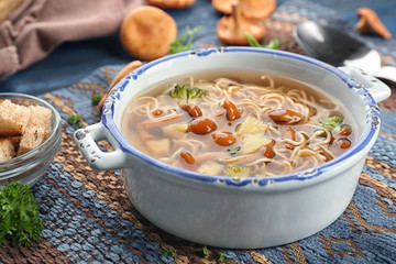 Dish with delicious mushroom soup on table