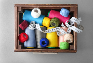 Wooden box with sewing threads and crocheting clews on grey background, top view