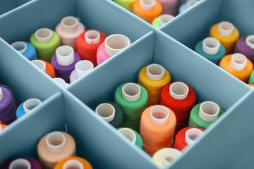 Set of color sewing threads in compartment box, closeup