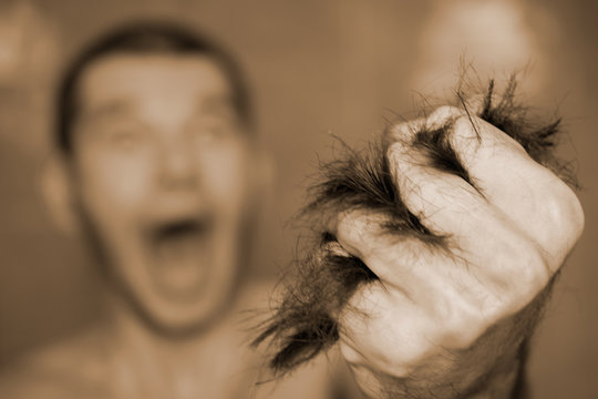 Close-up of torn scrap of dark hair in fist, looking crazy, screaming, desperate, angry, man, pulling his hair out. Extremes of human emotions. Selective focus , blurred background