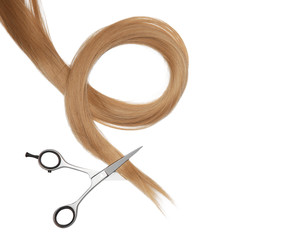 Professional hairdresser's scissors and strand of blonde hair on white background