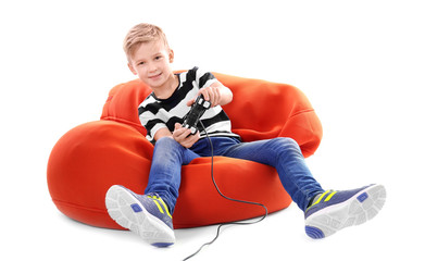 Cute boy playing video game on white background
