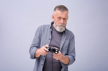 Emotional senior man playing video game on grey background