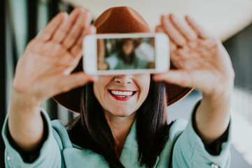 Young beautiful woman with brown hat taking herself a portrait with her cellphone making funny faces. Lifestyle photography