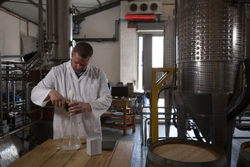 Male worker checking quality of gin