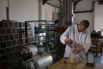 Worker checking quality of gin